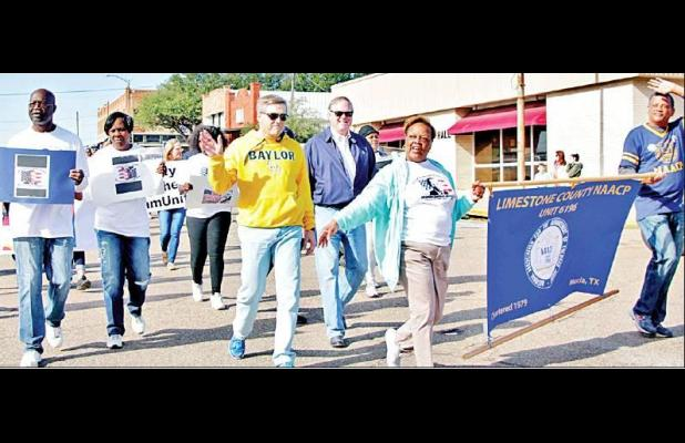 Limestone County NAACP President Rene Turner and Vice President David Echols, carrying the group's banner, are joined by County Attorney Roy DeFriend, 77th District Judge Patrick Simmons and other supporters in Saturday's MLK Day parade through downto